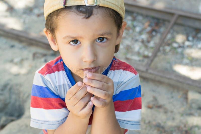 Junge, der im Yard mit einer Schnecke spielt lizenzfreies stockfoto
