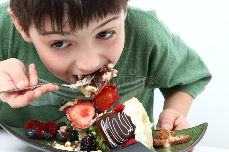 Junge, der Käsekuchen isst lizenzfreie stockfotografie