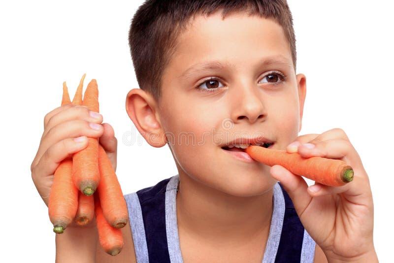 Junge, der Karotte isst stockfotografie