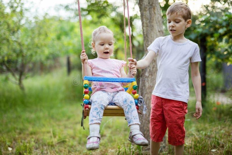Junge, der Kleinkindschwester auf Schwingen drückt stockbilder