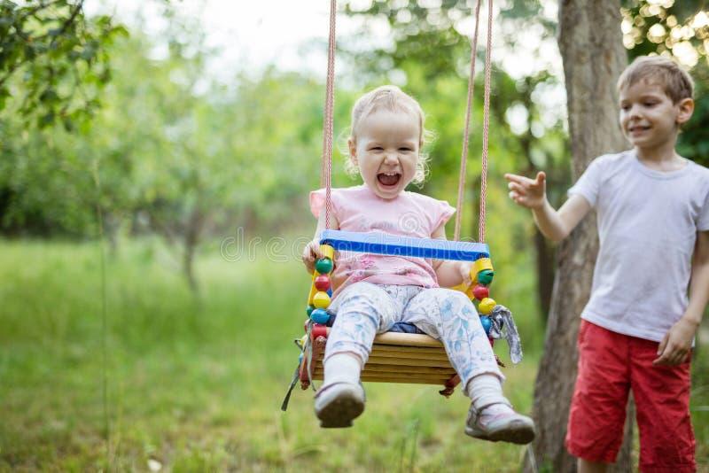 Junge, der Kleinkindschwester auf Schwingen drückt lizenzfreies stockfoto