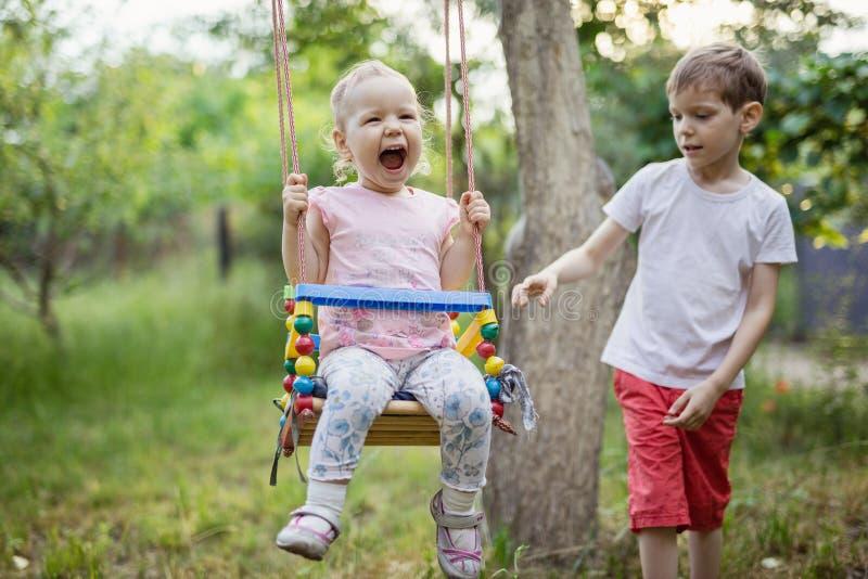 Junge, der Kleinkindschwester auf Schwingen drückt lizenzfreie stockbilder