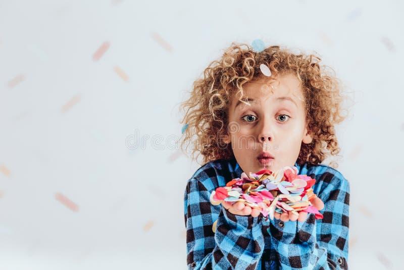 Junge, der Konfettis hält lizenzfreies stockbild