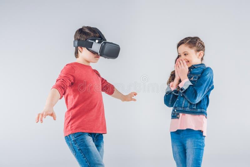 Junge, der Kopfhörer der virtuellen Realität während Mädchen schaut auf ihm verwendet stockfotos