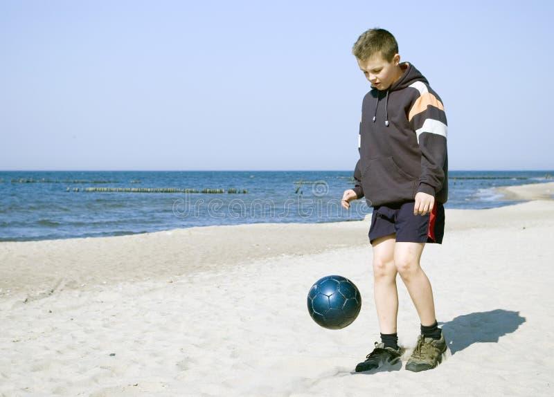 Junge, der Kugel auf Strand spielt. stockbilder