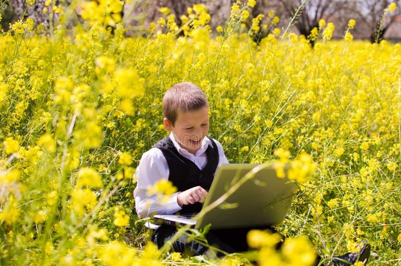 Junge, der an Laptop arbeitet stockbild