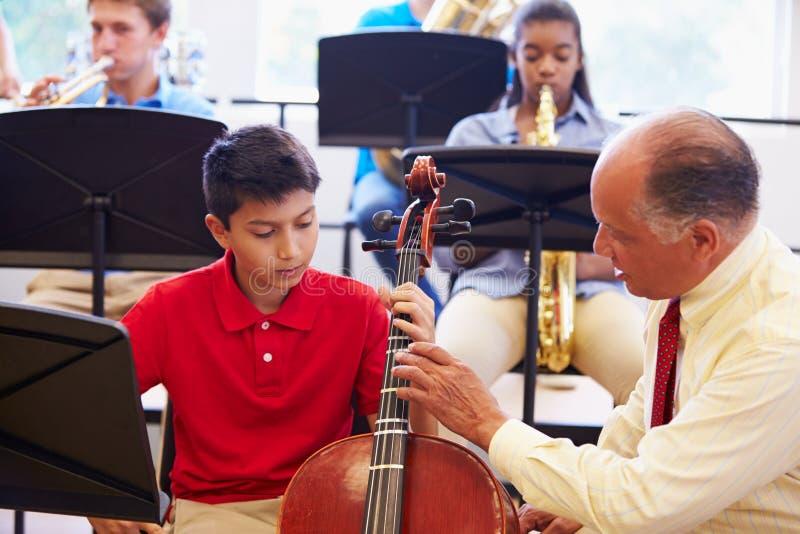 Junge, der lernt, Cello in Highschool Orchester zu spielen lizenzfreies stockfoto