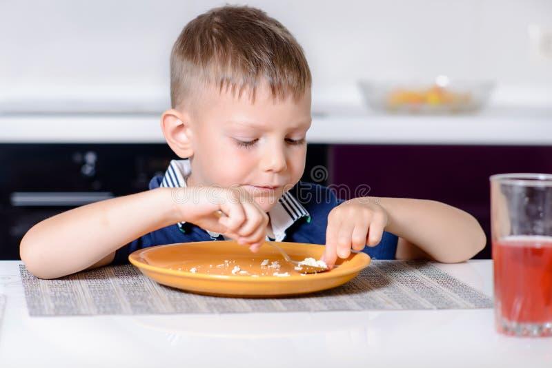Junge, der letzten Biss des Lebensmittels am Küchentisch isst stockfotografie