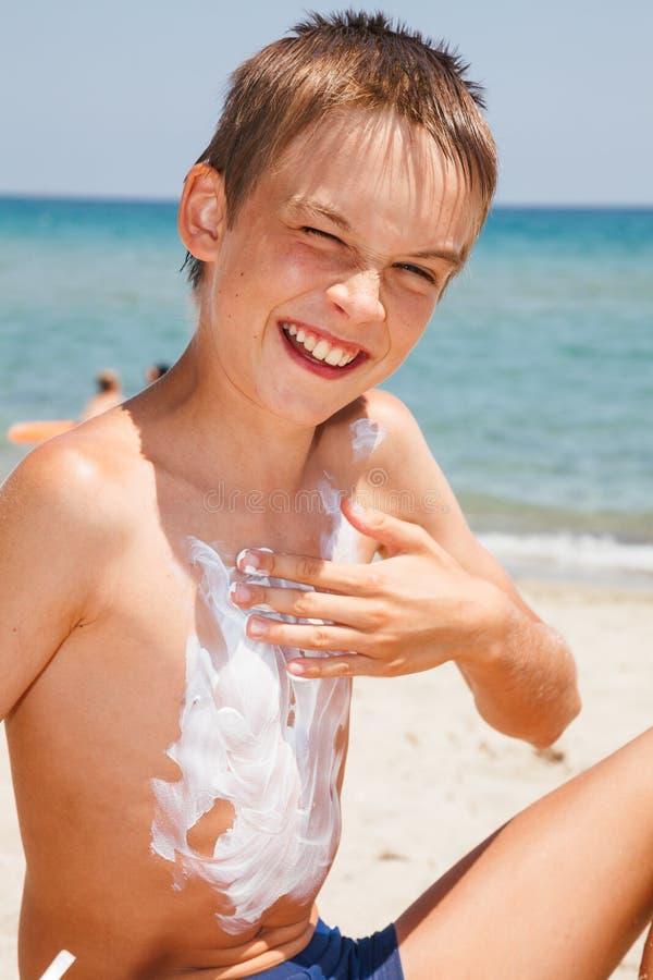 Junge, der Lichtschutz auf seinem Kasten an einem Strand anwendet stockfotos
