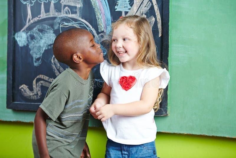 Junge, der Mädchen auf Backe küsst stockbild