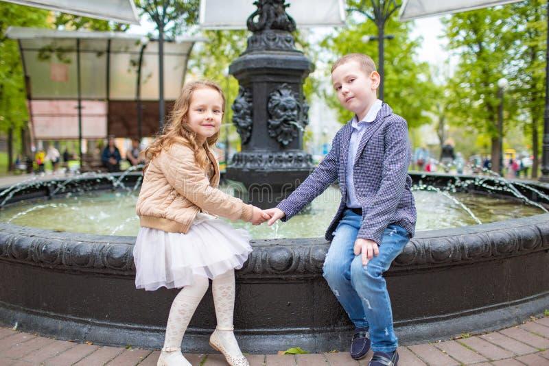 Junge, der Mädchen ` s Hand hält Kinder, die am Brunnen im Freien sitzen Liebesfreundschafts-Spaßkonzept Kleine Erwachsene stockbilder