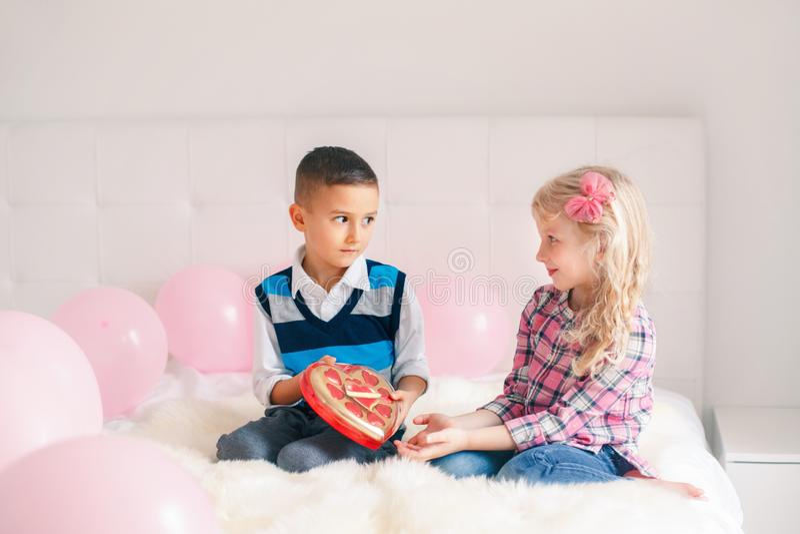 Junge, der Mädchenschokoladen-Geschenkgeschenk gibt, um Valentine Day zu feiern stockbilder
