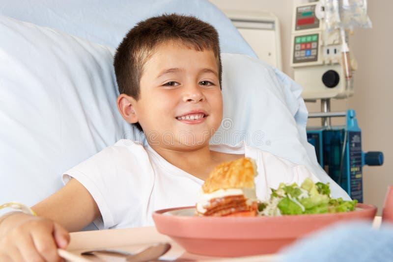 Junge, der Mahlzeit im Krankenhaus-Bett isst lizenzfreie stockfotografie
