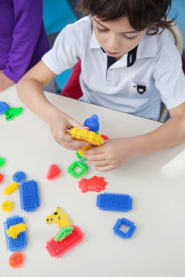 Junge, der mit Blöcken am Schreibtisch im Kindergarten spielt stockfotos