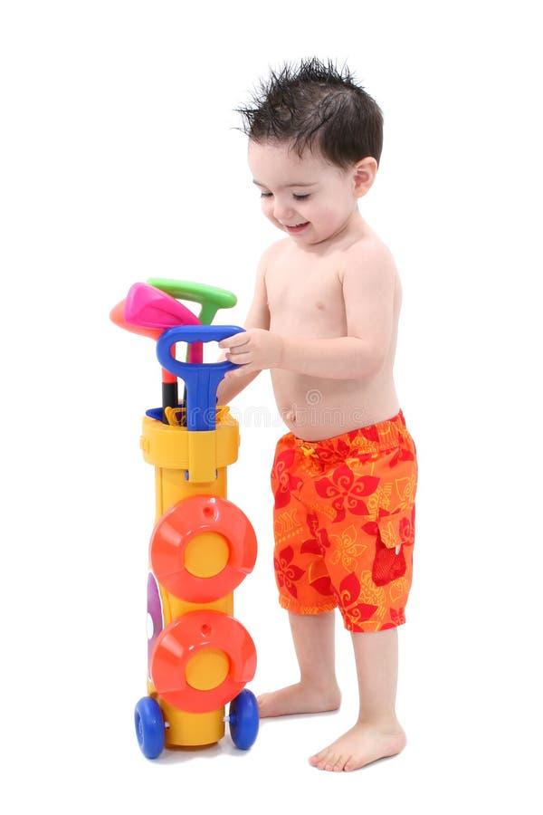 Junge, der mit dem Plastikgolf eingestellt über Weiß spielt stockbild