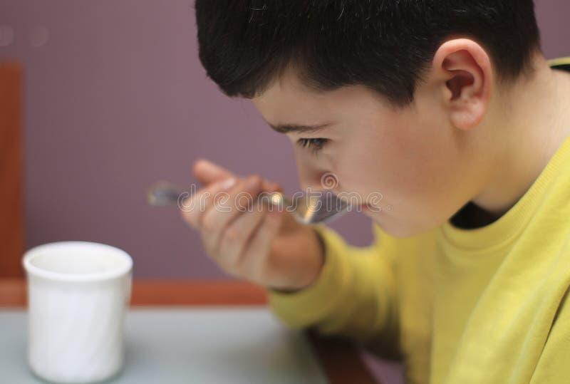 Junge, der mit einer Gabel am Tisch isst lizenzfreie stockfotografie