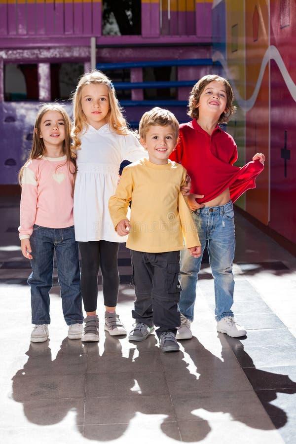 Junge, der mit Freunden im Kindergarten steht stockfotografie