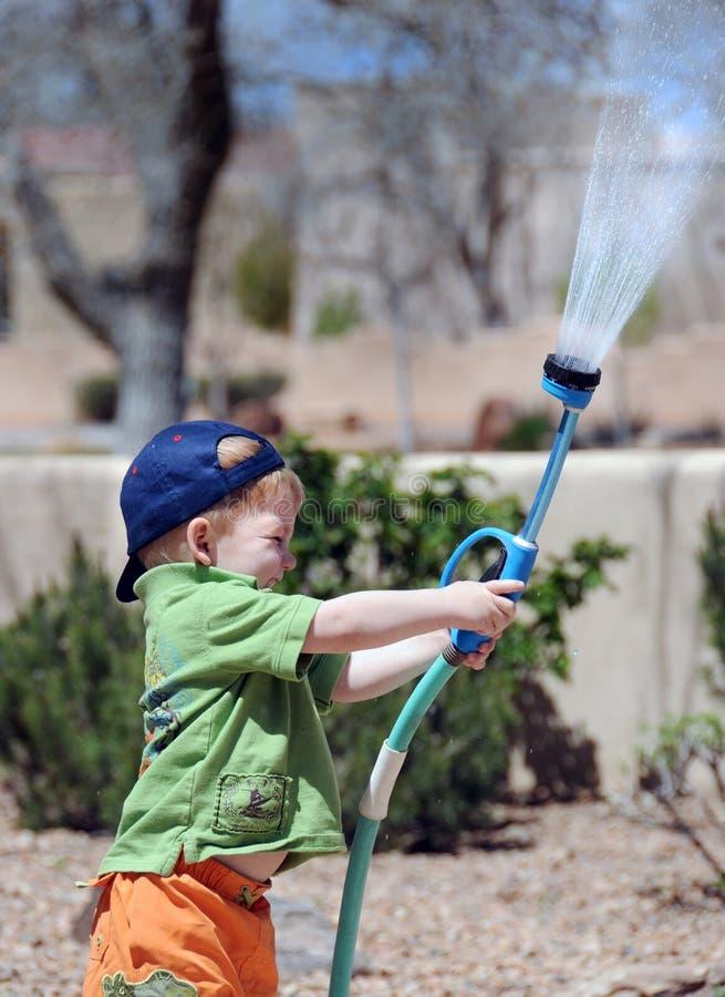 Junge, der mit Gartenschlauch spielt stockfotografie