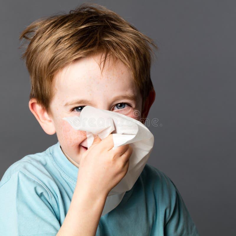 Junge, der mit Gewebe nach Kälte- oder Frühlingsallergien genießt lizenzfreie stockfotos