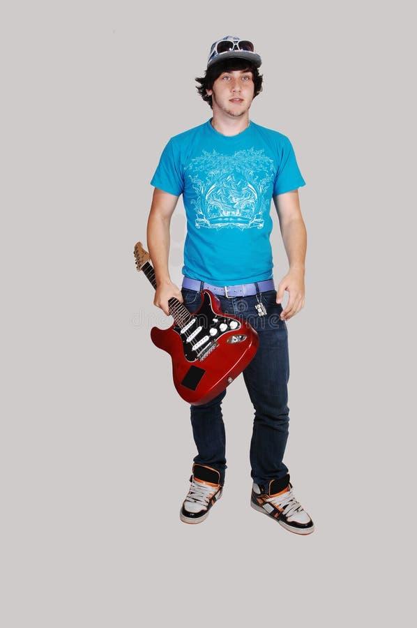 Junge, der mit Gitarre steht. stockbild