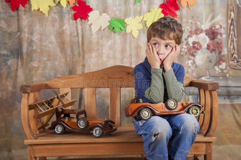 Junge, der mit hölzernen Spielzeugautos spielt stockbild
