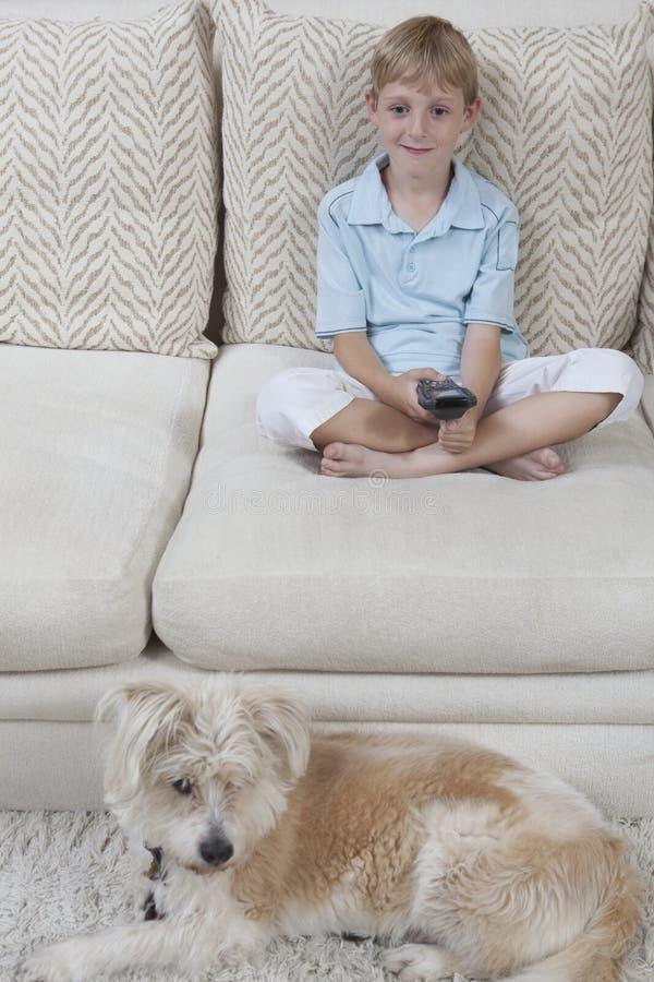 Junge, der Mit Hund fernsieht