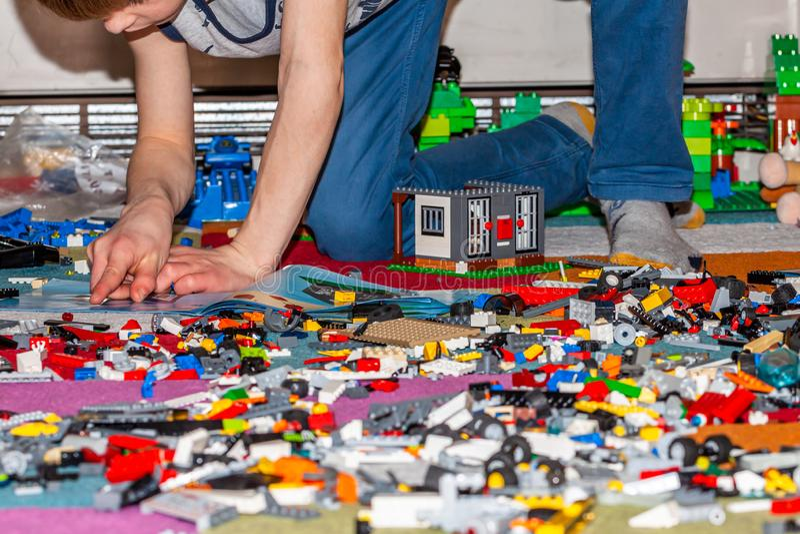 Junge, der mit Plastikbauspielwaren auf dem Boden spielt stockfoto