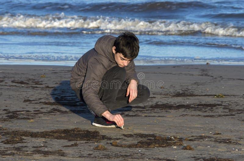 Junge, der mit Sand auf dem Strand spielt lizenzfreie stockfotografie