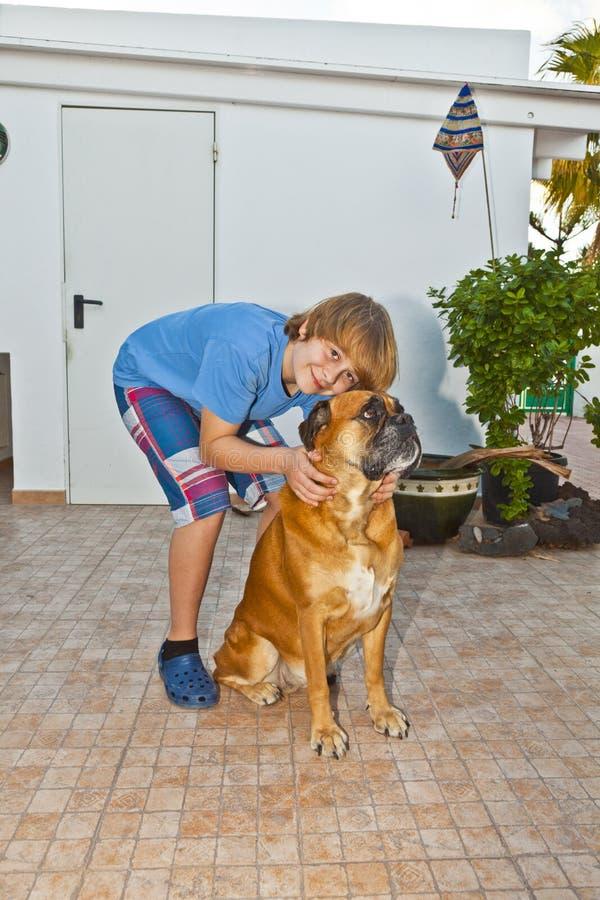 Junge, der mit seinem Hund spielt lizenzfreie stockfotos