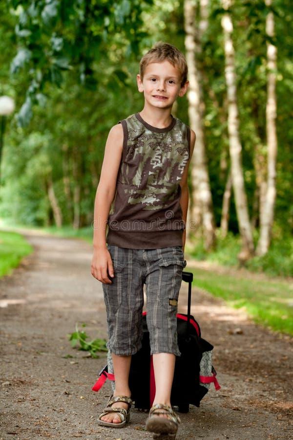 Junge, der mit seinem Koffer geht lizenzfreie stockfotografie