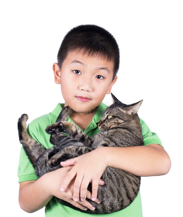 Junge, der mit seiner netten Tigerkatze lokalisiert auf weißem Hintergrund umarmt lizenzfreies stockfoto