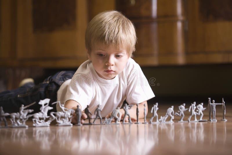 Junge, der mit Toy Soldiers On Floor spielt lizenzfreies stockbild