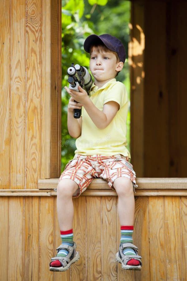 Junge, der mit Wasser-Pistolen im Park spielt stockbild
