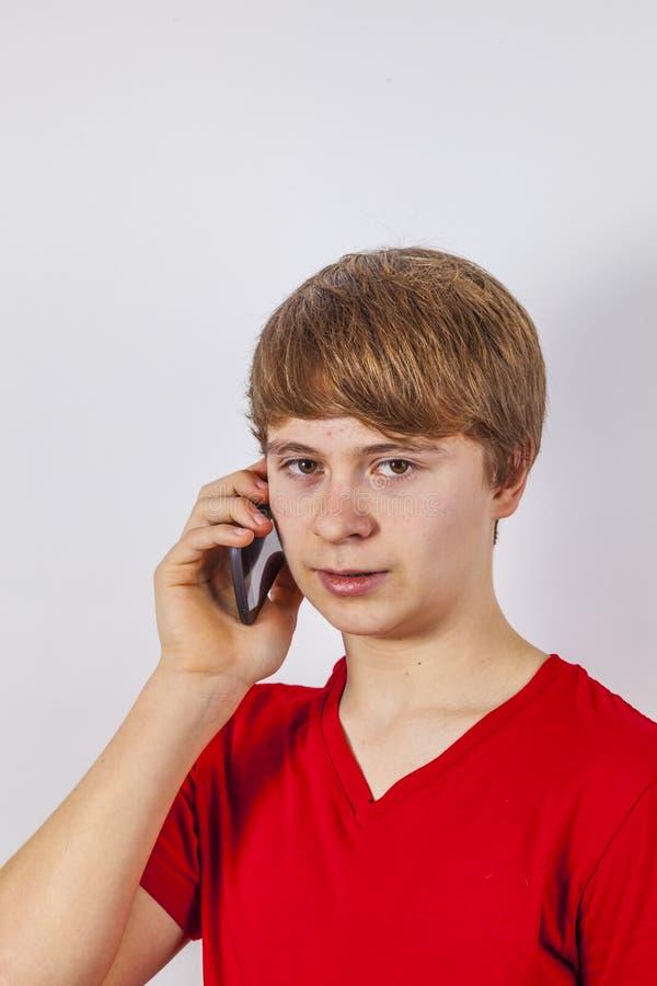 Junge, der am modernen Handy spricht lizenzfreie stockfotografie
