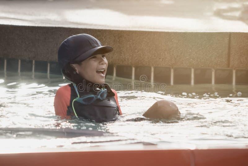 Junge, der nahe bei Wasserrutschen im Aquawasserpark siiting ist stockfoto