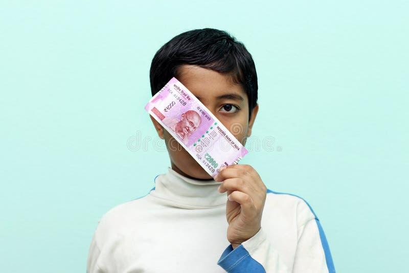 Junge, der 2000 neues indisches Geld der Rupie in seiner Hand hält lizenzfreie stockfotografie