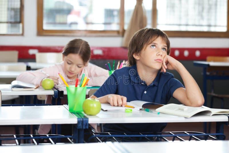 Junge, der oben im Klassenzimmer schaut lizenzfreies stockfoto