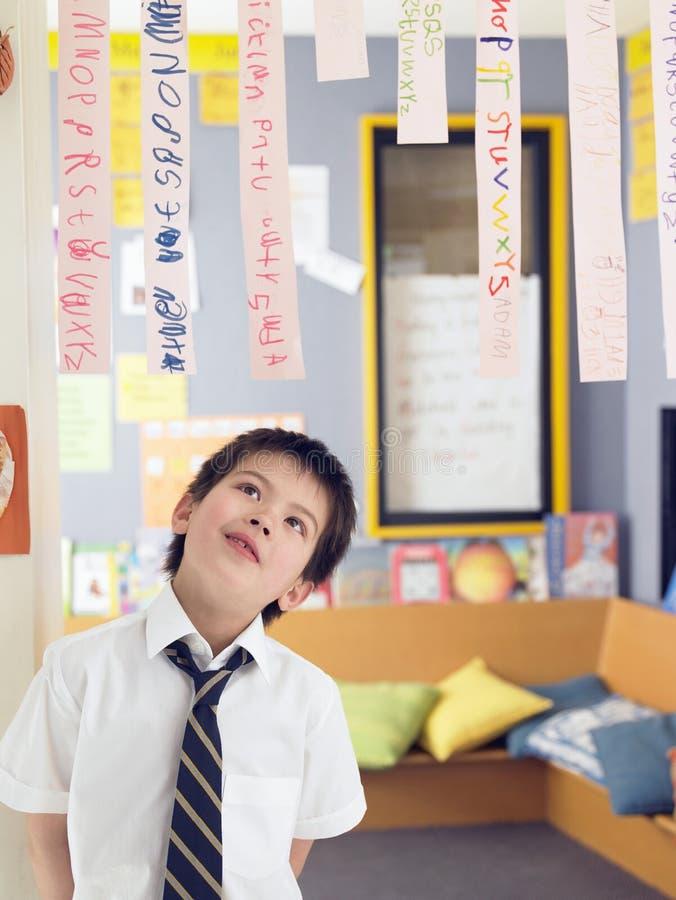 Junge, der oben Papierstreifen in der Klasse betrachtet stockfotos