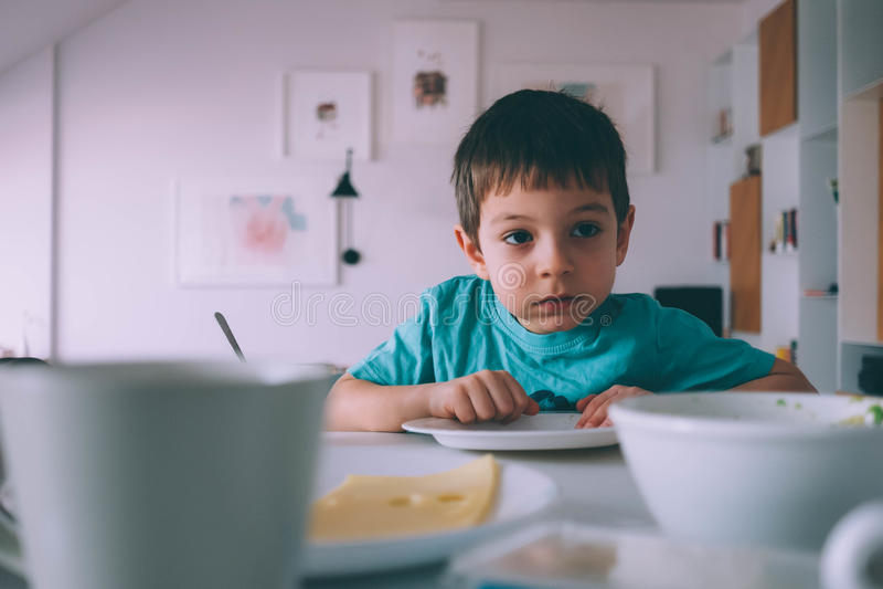 Junge, der ohne irgendeine Aufmerksamkeit isst stockfotos