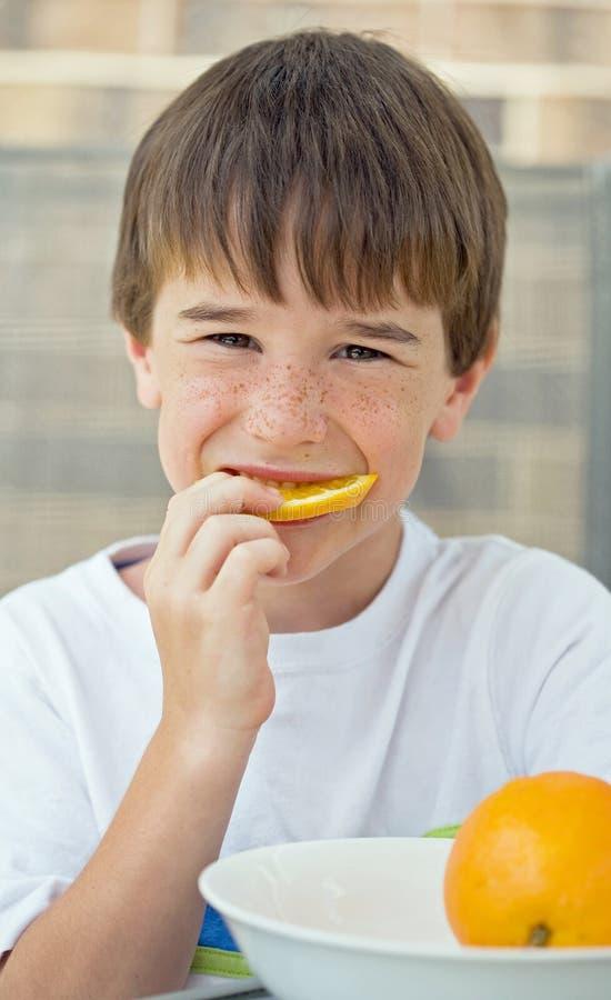 Junge, der orange Scheibe isst stockbild