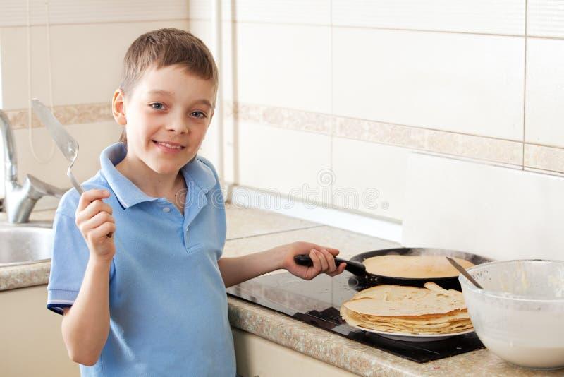 Junge, der Pfannkuchen kocht lizenzfreie stockfotos