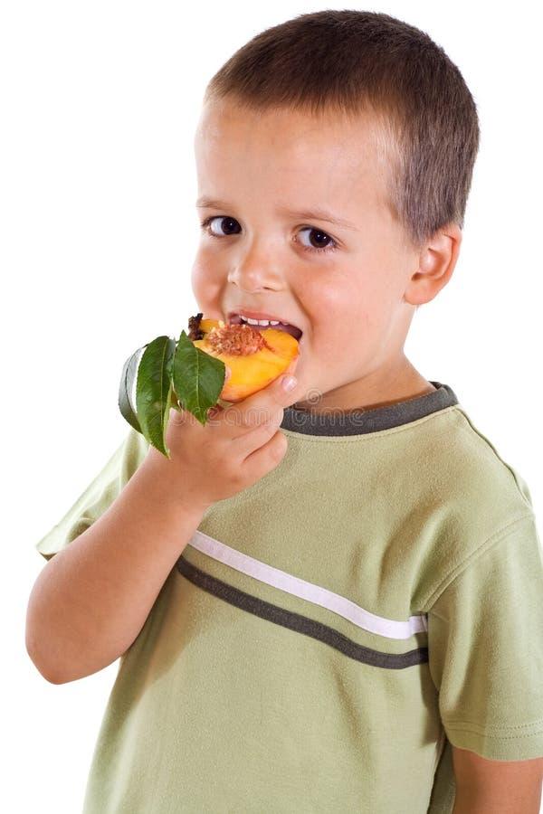 Junge, der Pfirsich isst stockfotos