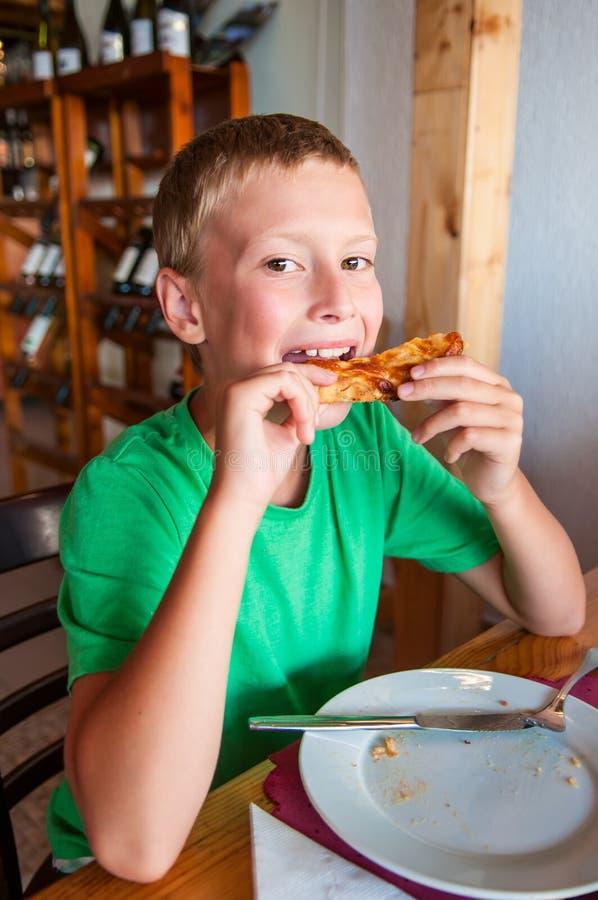 Junge, der Pizza isst lizenzfreies stockfoto