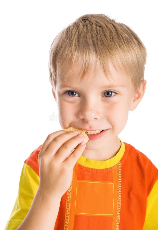 Junge, der Plätzchen isst stockfotografie