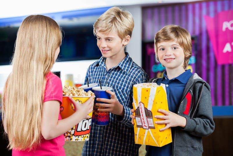 Junge, der Popcorn während Geschwister sprechen an hält stockbilder