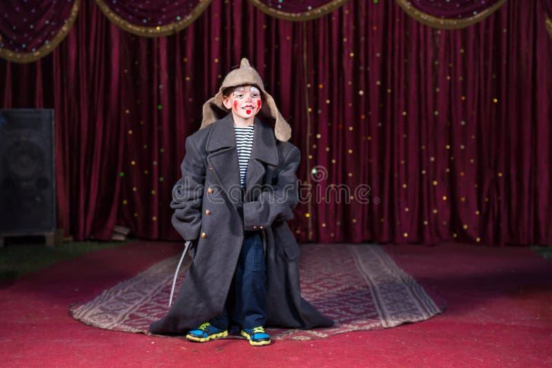 Junge, der Retro- Mantel und russischen Hut auf Stadium trägt lizenzfreie stockfotos