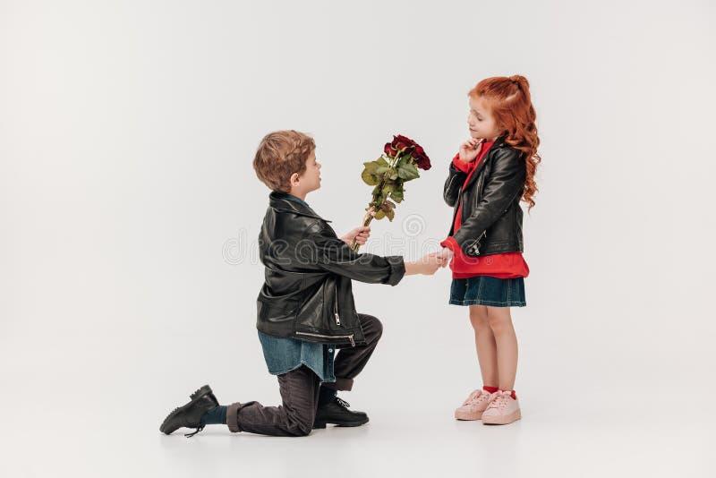 Junge, der Rosen Blumenstrauß seiner kleinen Freundin bei der Stellung auf Knie darstellt stockbild