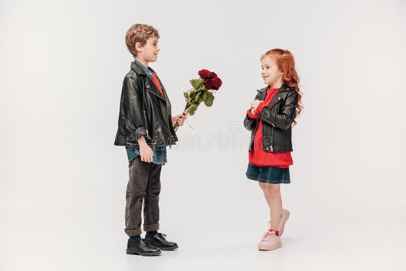 Junge, der Rosen Blumenstrauß seiner schönen kleinen Freundin darstellt lizenzfreie stockfotos
