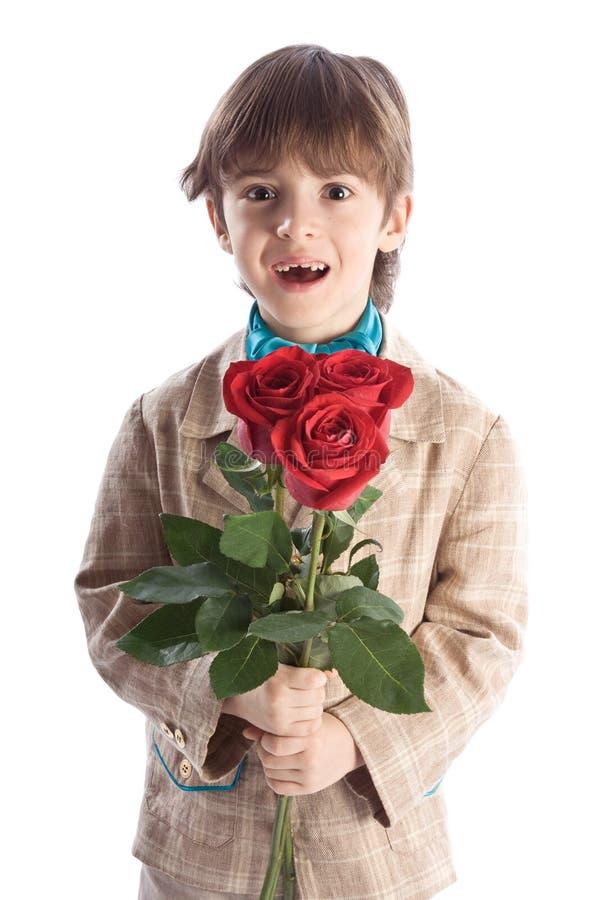 Junge, der rote Rosen anhält lizenzfreie stockfotos
