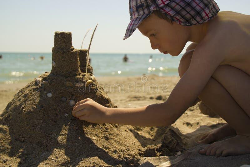 Junge, der Sandburg am Strand macht stockbilder